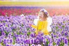 Liten flicka i den felika dräkten som spelar i blommafält Fotografering för Bildbyråer