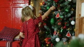 Liten flicka i den röda klänningen som hänger på julgranleksaker lager videofilmer