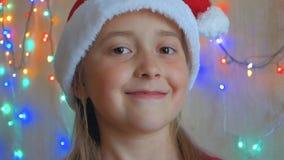 Liten flicka i den Santa Claus hatten på bakgrunden av att blinka girlander Tonåriga gulliga leenden för flicka på bakgrunden av  arkivfilmer