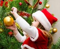Liten flicka i den santa hatten som dekorerar julträdet Royaltyfri Foto