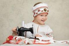 Liten flicka i den traditionella ryssskjortan och kokoshnik på processen av sömnaden Royaltyfria Bilder