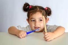 Liten flicka i den vita skjortan som rymmer bambutandborsten och den plast- tandborsten royaltyfri bild