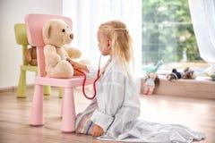 Liten flicka i det medicinska laget som spelar med nallebjörnen arkivfoton