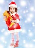 Liten flicka i dräkt av Santa Claus med gåvan Arkivbilder