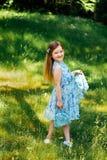 Liten flicka i en blå klänning med en blå påse i sommarträdgård Arkivbild