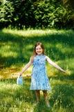 Liten flicka i en blå klänning med en blå påse i sommarträdgård Fotografering för Bildbyråer