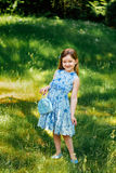 Liten flicka i en blå klänning med en blå påse i sommarträdgård Arkivfoto
