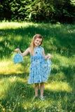 Liten flicka i en blå klänning med en blå påse i sommarträdgård Royaltyfri Foto