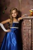 Liten flicka i en elegant blåttklänning Fotografering för Bildbyråer