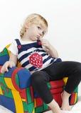 Liten flicka i en färgrik fåtölj Arkivfoto