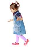 Liten flicka i en grov bomullstvillklänning på vit bakgrund Royaltyfri Foto