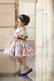 Liten flicka i en härlig klänning nära väggen utomhus Arkivfoton