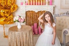 Liten flicka i en härlig vit klänning i inre Royaltyfri Foto