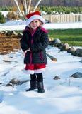 liten flicka i en jultomtenhatt som spelar i snö Arkivbild
