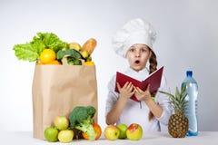 Liten flicka i en lockkock en variation av ny mat Flickan rymmer den röda boken i händer Mirakel- mänsklig sinnesrörelse, ansikts royaltyfri fotografi