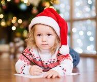 Liten flicka i en röd julhatt som skrivar ett brev till Santa Cla Arkivbild