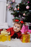 Liten flicka i en röd klänning på bakgrund av julgranen arkivbilder