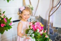 Liten flicka i en rosa klänning nära rosa blommor Royaltyfri Fotografi