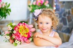 Liten flicka i en rosa klänning nära rosa blommor Fotografering för Bildbyråer