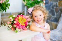 Liten flicka i en rosa klänning nära rosa blommor Royaltyfria Bilder