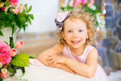 Liten flicka i en rosa klänning nära rosa blommor Arkivfoton