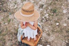 Liten flicka i en stol utomhus Arkivfoto