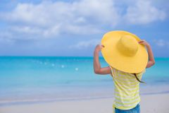 Liten flicka i en stor gul sugrörhatt på vit Arkivbild