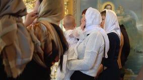 Liten flicka i en vit dop- klänning i hennes moders armar lager videofilmer