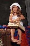 Liten flicka i en vit   hattbladsida av boken på mörka lodisar Royaltyfri Foto