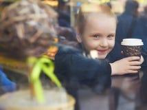 Liten flicka i ett kafé med en pappers- kopp Royaltyfri Foto