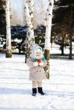 Liten flicka i ett pälslag och fluffiga Orenburg sjalar med en app Royaltyfri Bild