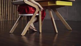 Liten flicka, i ett rött kjolsammanträde på ett skrivbord och att vinka hennes kala fot lager videofilmer