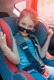Liten flicka i ett säkerhetsbilsäte Säkerhet och trygghet Säker driv royaltyfri foto