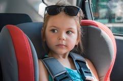 Liten flicka i ett säkerhetsbilsäte Säkerhet och trygghet Säker driv royaltyfria bilder