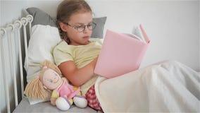 Liten flicka i exponeringsglas som läser en bok, medan ligga i säng Bredvid henne sitter en docka arkivfilmer