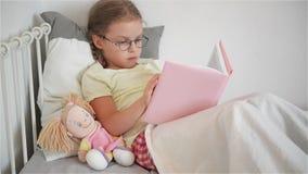 Liten flicka i exponeringsglas som läser en bok, medan ligga i säng Bredvid henne sitter en docka stock video
