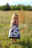 Liten flicka i fält av vildblommor Arkivbilder
