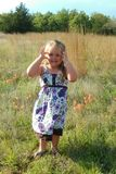 Liten flicka i fält av vildblommor Royaltyfria Bilder