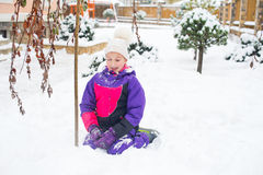 Liten flicka i färgrik dräktlek i insnöad bakgård i förkylning Royaltyfri Fotografi