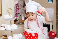 Liten flicka i förkläde i köket. Arkivfoto