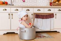 Liten flicka i förkläde i köket Arkivbild
