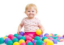 Liten flicka i färgade bollar för bollgrop woth Arkivfoton