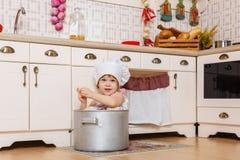 Liten flicka i förkläde i köket Arkivbilder