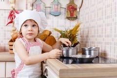 Liten flicka i förkläde i köket Royaltyfri Foto