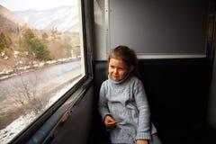 Liten flicka i grå tröja som reser med det Kukushka drevet i Georgia och ser genom hela fönstret arkivbild