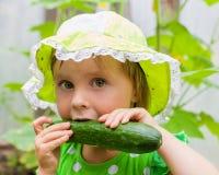 Liten flicka i grön hatt som äter den nya gurkan Arkivfoton