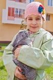 Liten flicka i grönaktig omslagshållkanin royaltyfria foton