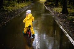 Liten flicka i gul vattentät kläder på cykeln Royaltyfria Foton