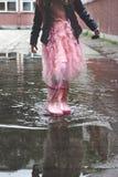 Liten flicka i gummistöveler som spelar i liten pöl efter regn arkivfoto