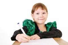 Liten flicka i härlig grön klänning med pennan i hand Arkivfoto